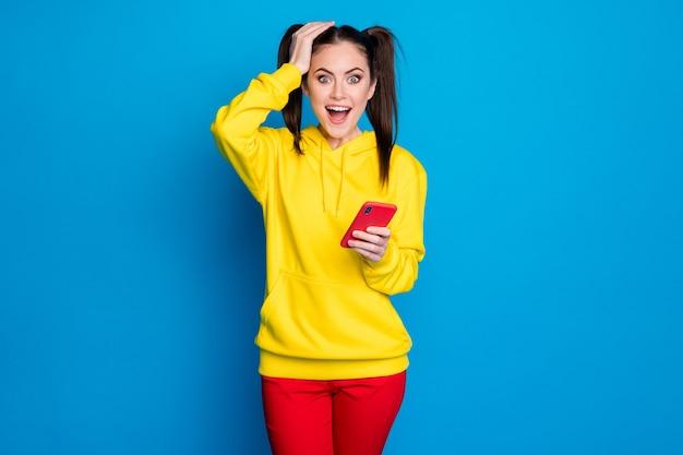 Portret jej jest ładna atrakcyjna całkiem urocza szczęśliwa wesoła wesoła dziewczyna za pomocą urządzenia komórkowego 5g aplikacja smm czytanie wygrana zwycięzca powiadomienie na białym tle nad jasnym żywym połyskiem żywy niebieski kolor tła