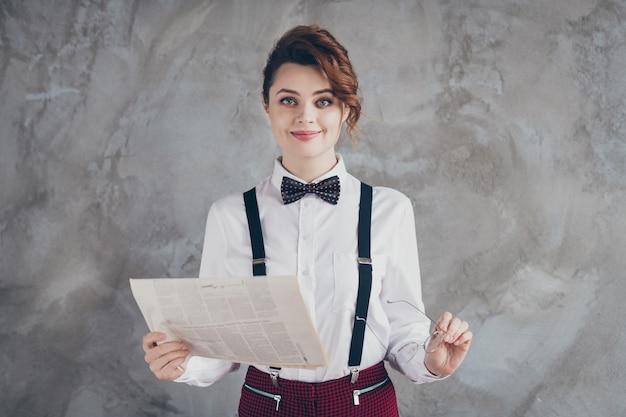 Portret jej jest ładna, atrakcyjna, ładna, inteligentna, sprytna, wesoła, falowana dziewczyna czytająca finanse wiadomości ze świata na białym tle na szarym betonowym tle ściany przemysłowej