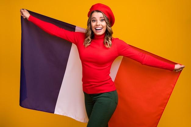 Portret jej jest ładna, atrakcyjna, śliczna, urocza, wesoła, falowana dziewczyna trzymająca w rękach francuską flagę, bawiącą się na jasnym, żywym połysku, żywy, żółty kolor tła