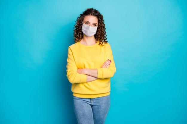 Portret jej jest ładna atrakcyjna treść zdrowa dziewczyna z falistymi włosami nosi maskę bezpieczeństwa założonymi rękami zatrzymaj grypę grypę skażenie na białym tle jasny żywy połysk żywy niebieski kolor tła