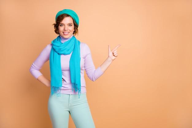 Portret jej jest ładna, atrakcyjna, urocza, całkiem wesoła, wesoła dziewczyna demonstrująca reklamę nową nowość na białym tle na beżowym pastelowym kolorze