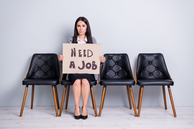 Portret jej jest miła atrakcyjna biedna nieszczęśliwa przygnębiony zwolniony pani kierownik biura urzędnik siedzi na krześle trzymając plakat szukam redukcji kosztów pracy na białym tle pastelowy szary kolor tła