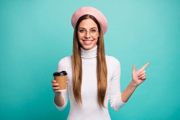 Portret jej jest miła, atrakcyjna, dość wesoła, wesoła, prostowłosa dziewczyna pijąca latte, wykazująca kopię pustej przestrzeni reklama na białym tle nad jasnym żywym połyskiem żywy niebieski kolor tła