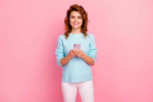 Portret jej jest miła, atrakcyjna, urocza, urocza, całkiem wesoła, wesoła, falowana dziewczyna za pomocą cyfrowego gadżetu nowoczesnej technologii na białym tle nad różowym pastelowym kolorem tła