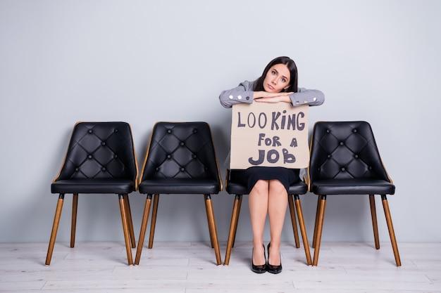 Portret jej jest miła, atrakcyjna, znudzona, przygnębiona, zwolniona pani, kierownik sprzedaży, dyrektor finansów, siedząc w fotelu, trzymając plakat promocyjny, szukając pracy kryzys gospodarki na białym tle pastelowy szary kolor tła