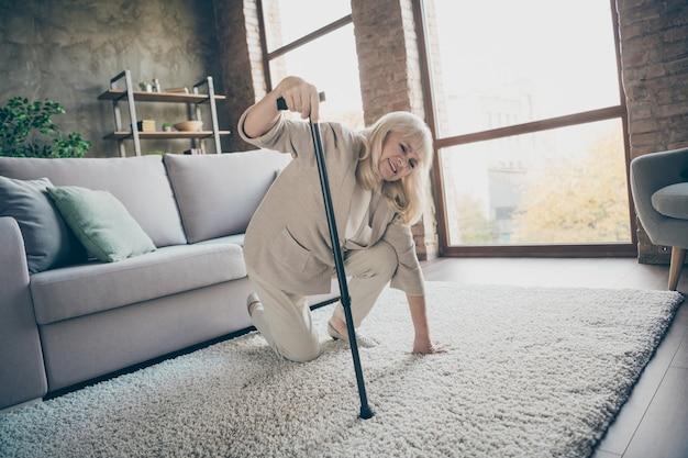 Portret jej ładna atrakcyjna chora, siwowłosa babcia próbuje wstać, opierając się na patyku, czując się źle cierpiąc w industrialnym ceglanym lofcie w nowoczesnym stylu