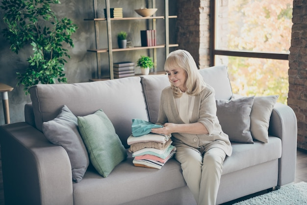 Portret jej ładna atrakcyjna miła pracowita siwowłosa babcia siedzi na sofie składane rzeczy rzeczy obowiązek odzieżowy w industrialnym ceglanym lofcie nowoczesny styl wnętrze domu mieszkanie