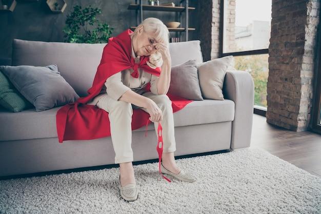 Portret jej ładna atrakcyjna zmęczona chora chora siwowłosa blondynka babcia w czerwonym kostiumie siedzi na kanapie po ratowaniu planety w industrialnym ceglanym lofcie nowoczesny styl wnętrze domu mieszkanie