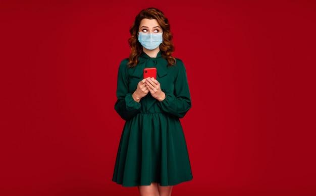 Portret jej ładnej atrakcyjnej falistowłosej dziewczyny noszącej maskę z gazy za pomocą urządzenia patrząc na bok kopiować przestrzeń na białym tle jasny żywy połysk żywy czerwony bordowy kolor tła
