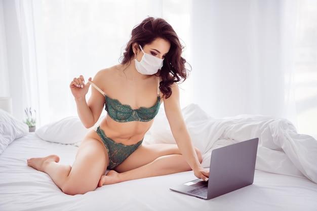 Portret jej ładnej szczupłej sportowej atrakcyjnej pociągającej dziewczyny siedzącej na łóżku pozującej rozbieranie porno porno xxx w masce z gazy w jasnym białym wnętrzu dom apartament hotel