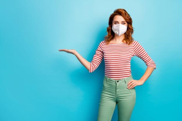 Portret jej ona atrakcyjna imbirowa lisica nosi maskę bezpieczeństwa trzymając miejsce na kopię na dłoni zanieczyszczenie powietrza problem co2 mers cov choroba na białym tle jasny żywy żywy niebieski kolor tła