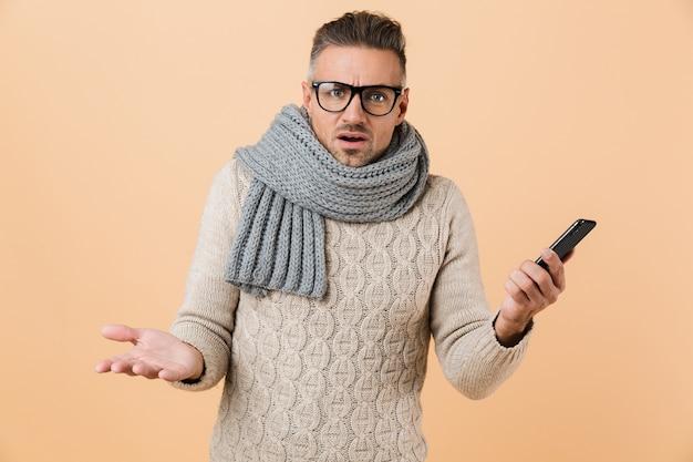 Portret, jeśli sfrustrowany mężczyzna ubrany w sweter i szalik stojący na białym tle nad beżową ścianą, trzymając telefon komórkowy