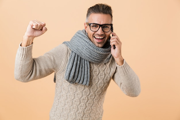 Portret, jeśli szczęśliwy mężczyzna ubrany w sweter i szalik stoi na białym tle nad beżową ścianą, rozmawia przez telefon komórkowy, świętuje