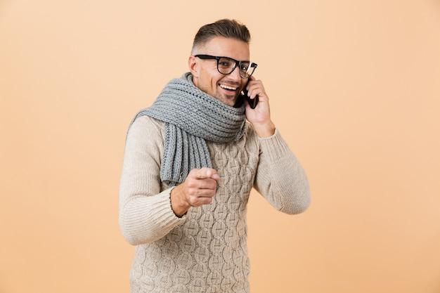 Portret, jeśli uśmiechnięty mężczyzna ubrany w sweter i szalik stoi na białym tle nad beżową ścianą, rozmawia przez telefon komórkowy, świętuje
