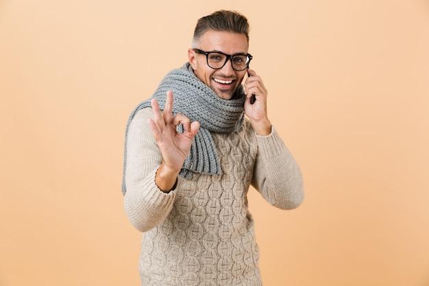 Portret, jeśli uśmiechnięty mężczyzna ubrany w sweter i szalik stoi odizolowany na beżowej ścianie, rozmawia przez telefon komórkowy, pokazuje ok