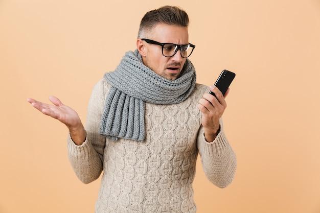 Portret, jeśli zdezorientowany mężczyzna ubrany w sweter i szalik stoi na białym tle nad beżową ścianą, trzymając telefon komórkowy
