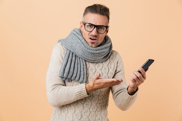 Portret, jeśli zdziwiony mężczyzna ubrany w sweter i szalik stoi odizolowany na beżowej ścianie, trzymając telefon komórkowy
