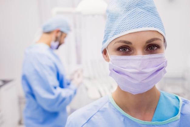 Portret jest ubranym chirurgicznie maskę żeński dentysta