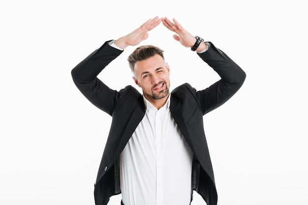 Portret jest ubranym czarną kurtkę mruga i gestykuluje pomyślny mężczyzna jest ubranym nad kamerą podczas gdy ono uśmiecha się, odizolowywający nad bielem