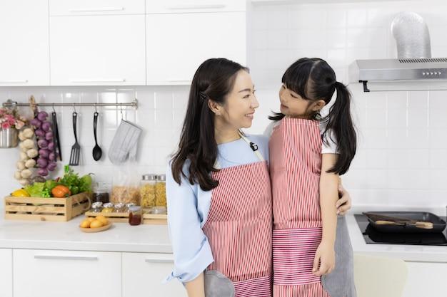 Portret jest ubranym fartuchy w kuchni azjatykcia rodzina