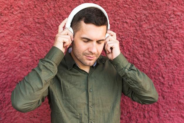 Portret jest ubranym hełmofon słuchającą muzykę mężczyzna