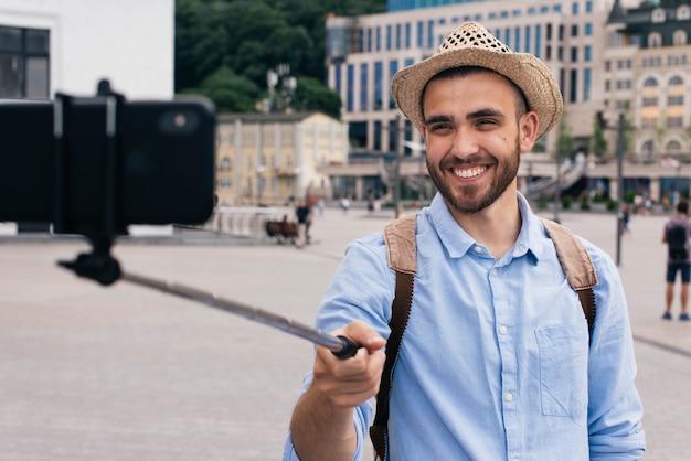 Portret jest ubranym kapelusz szczęśliwego mężczyzna bierze selfie przy outdoors