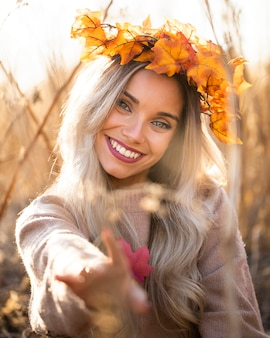Portret jest ubranym liść klonowy wianek przy outdoors uśmiechnięta kobieta