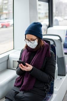 Portret jest ubranym maskę chirurgiczną w transporcie publicznym dorosła kobieta