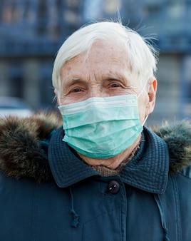 Portret jest ubranym medyczną maskę stara kobieta podczas gdy w mieście