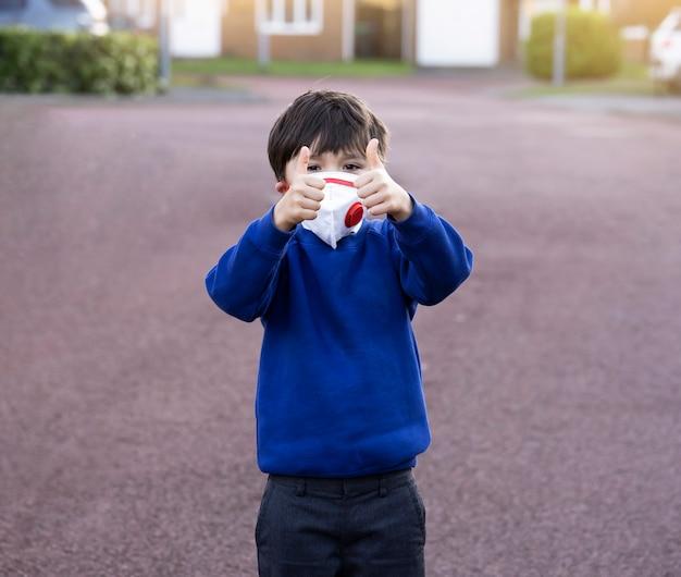Portret jest ubranym ochronną twarz maskę dla zanieczyszczenia lub wirusa szkolny dzieciak, dziecko jest ubranym maskę ochronną i pokazuje aprobaty w mundurku szkolnym podczas gdy czekający autobus szkolnego w ranku.