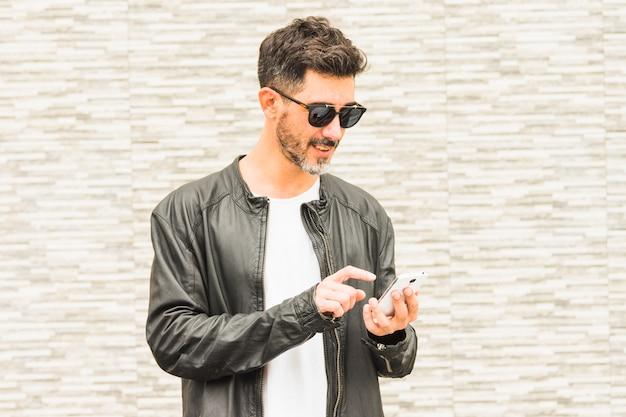 Portret jest ubranym okulary przeciwsłonecznych używać smartphone przystojny młody człowiek