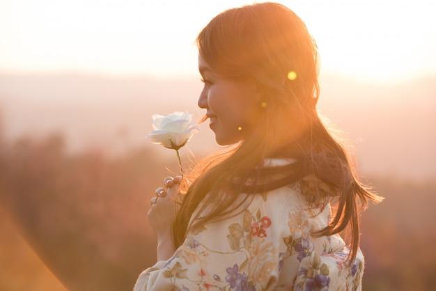 Portret jest ubranym tradycyjnego japońskiego kimono azjatycka kobieta i ręki trzyma pięknej białej róży, przed zmierzchem, miłości pojęcie.