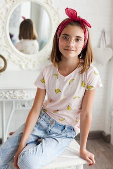Portret jest ubranym widowiska obsiadanie na stołowej patrzeje kamerze dziewczyna