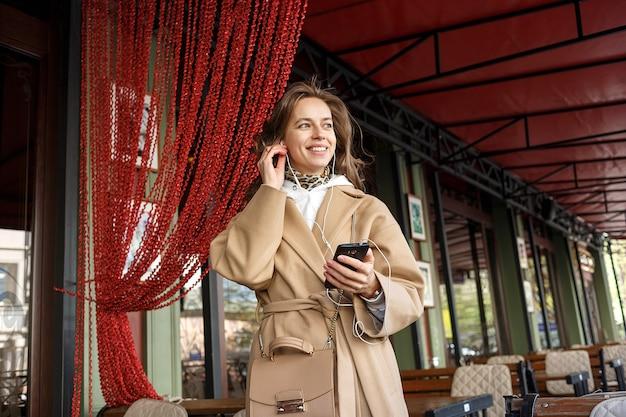 Portret jest ubranym żakiet słucha muzyka na cukiernianej werandzie z słuchawkami trzyma telefon komórkowego w rękach młoda dziewczyna