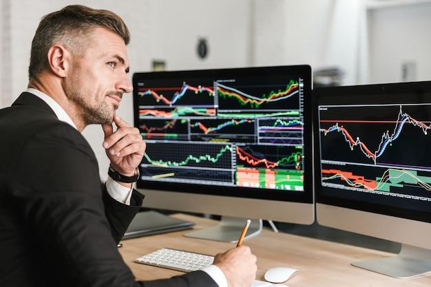 Portret kaukaski biznesmen 30s ubrany w garnitur, pracujący w biurze i patrząc na komputerze z grafiką i wykresami na ekranie