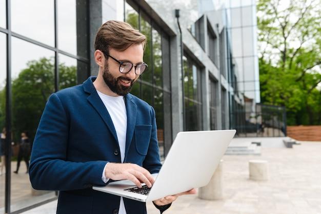 Portret kaukaski biznesmen noszenie okularów przy użyciu i patrząc na laptopa, stojąc na zewnątrz w pobliżu budynku