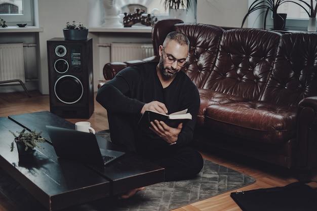 Portret kaukaski facet pisze na notebooku, kopiując z laptopa i siedząc na podłodze w luksusowym salonie.