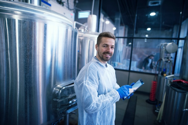 Portret kaukaski mężczyzna w białym garniturze stojącego nad zbiornikami w zakładzie produkcyjnym pracownik przemysłowy z tabletem
