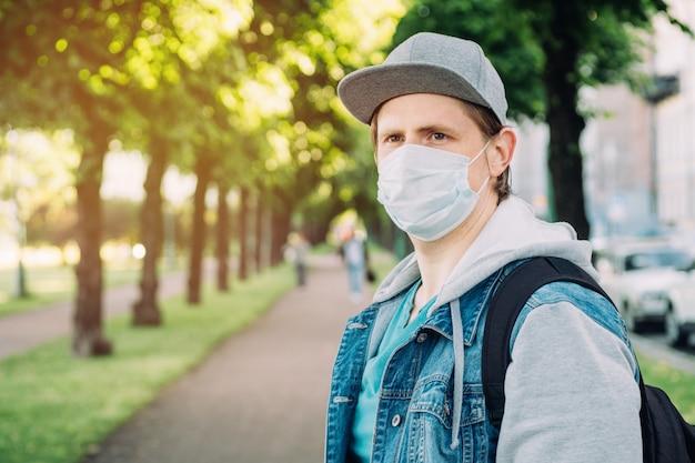 Portret kaukaski mężczyzna w medycznej masce i nakrętce podczas pandemii w mieście z kopii przestrzenią. nowa normalna