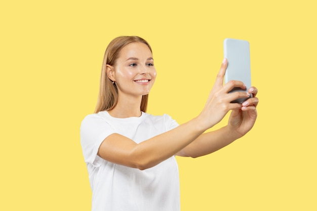 Portret kaukaski młoda kobieta w połowie długości na żółtym studio