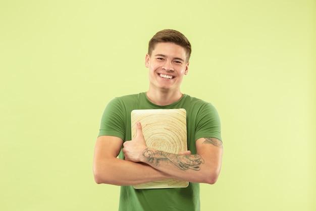 Portret kaukaski młody człowiek w połowie długości na zielonym studio