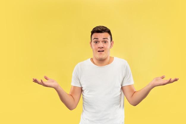 Portret kaukaski młody człowiek w połowie długości na żółtym tle studio. piękny męski model w koszuli. pojęcie ludzkich emocji, wyraz twarzy, sprzedaż, reklama. pokazanie czegoś, wygląda na niepewne.