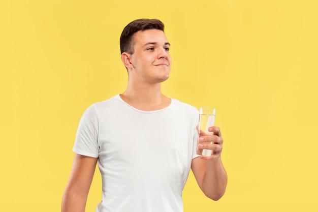Portret kaukaski młody człowiek w połowie długości na żółtym tle studio. piękny męski model w koszuli. pojęcie ludzkich emocji, wyraz twarzy, sprzedaż, reklama. radość z picia czystej wody.