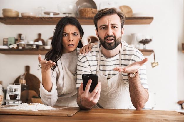 Portret kaukaski para mężczyzna i kobieta 30 lat w fartuchach czyta przepis podczas gotowania ciasta z mąką i jajkami w kuchni w domu