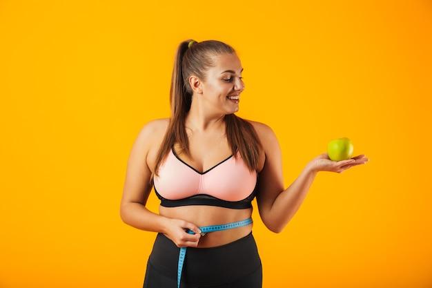 Portret kaukaski pulchna kobieta w stanik sportowy mierzący jej talię miernikiem i trzymając jabłko, na białym tle na żółtym tle