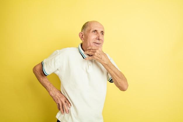 Portret kaukaski starszego mężczyzny na białym tle studio żółty