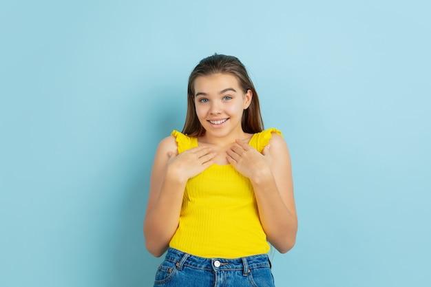Portret Kaukaski Teen Girl Na Białym Tle Na Niebieskim Tle. Piękny Model W Swobodnym żółtym Kolorze. Darmowe Zdjęcia