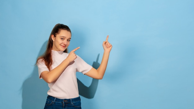 Portret kaukaski teen girl wyizolowanych w niebieskim studio