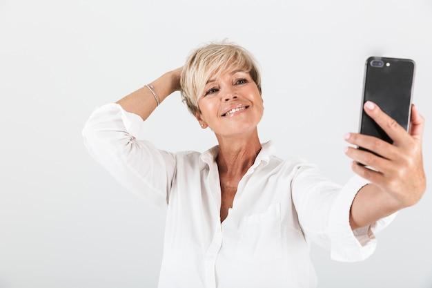 Portret kaukaskiej dorosłej kobiety z krótkimi blond włosami uśmiecha się i robi selfie portret na telefonie komórkowym izolowanym nad białą ścianą w studio