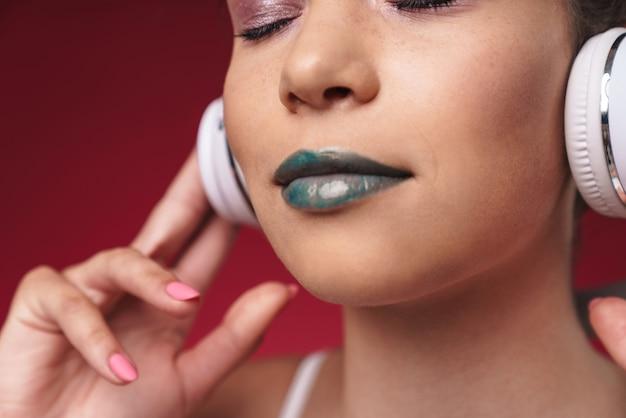 Portret kaukaskiej dziewczyny punkowej z dziwaczną fryzurą i zamkniętymi oczami, słuchającej muzyki przez słuchawki izolowane nad czerwoną ścianą